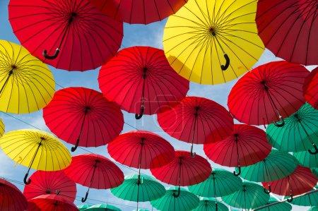 Photo pour Parapluies de rouges, verts et jaunes vives sur fond de ciel nuageux - image libre de droit