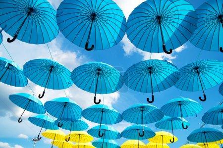 Photo pour Parasols bleus et jaunes vives sur fond de ciel nuageux - image libre de droit