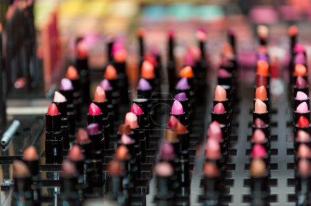 Photo pour Beau maquillage professionnel multicolor gros ensemble de nombreux rouges à lèvres colorés différents dans des tubes en plastique noirs en vitrine, image horizontale - image libre de droit