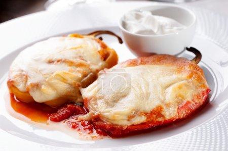 Foto de Pimientos a la brasa y primer plano del queso fundido en plato blanco con crema agria - Imagen libre de derechos