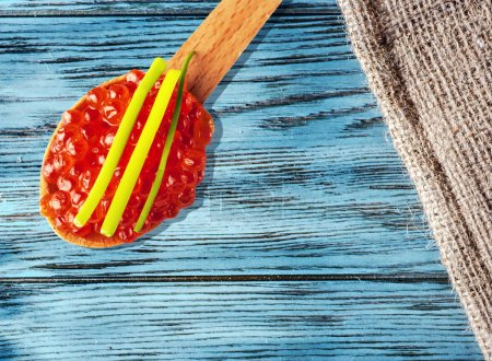 Red caviar on wooden table