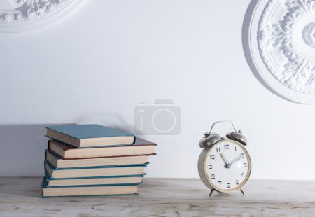Shelf with books and an alarm clock