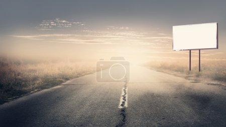Photo pour Panneau d'affichage sur la route pendant le coucher du soleil - image libre de droit