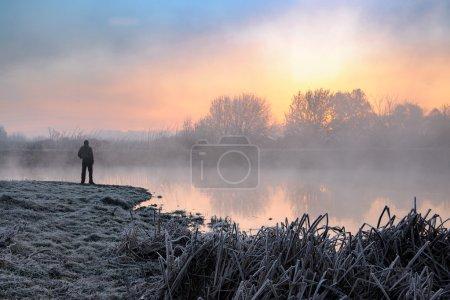 Man standing near lake