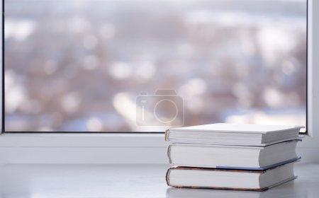 Books on window in winter