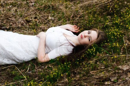 Beautiful innocent woman in white dress lying on the grass