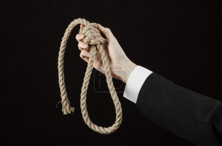 Suicide and business topic: Hand of a businessman in a black jacket holding a loop of rope for hanging on black isolated background
