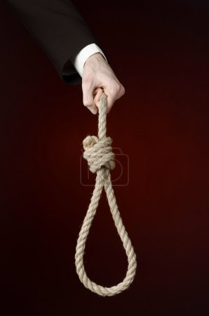Suicide and business topic: Hand of a businessman in a black jacket holding a loop of rope for hanging on dark red isolated background
