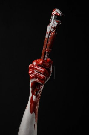 Bloody hand holding an adjustable wrench, bloody key, crazy plumber, bloody theme, halloween theme, black background,isolated , bloody hand of an assassin, bloody murderer, psycho,bloody monkey wrench
