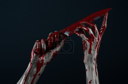 Bloody Halloween theme: zombie killer holding a large bloody knife isolated on black background in studio.