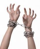 Sociální téma: ruce svázané kovový řetízek na bílém pozadí