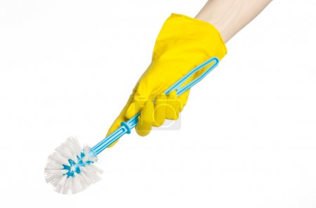 Cleaning the house and cleaning the toilet: human hand holding a blue toilet brush in yellow protective gloves isolated on a white background in studio