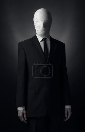 Photo for Internet meme and terrible character Halloween theme: very tall burly man with long arms in a suit with bandaged face fabric, an unknown killer in the suit, The Slender Man, Secret legend of the city in studio - Royalty Free Image