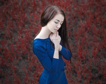 Un portrait dramatique d'un thème fille : portrait d'une belle fille dans la forêt dans une robe bleue sur un fond d'herbe rouge