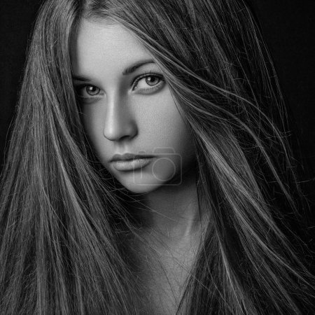 Dramatic portrait of a girl theme: portrait of a beautiful lonely girl with flying hair in the wind isolated on dark background in studio