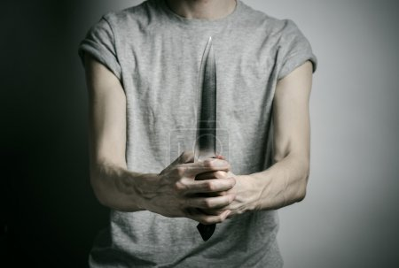 Murder and Halloween theme: a man holding a knife on a gray background