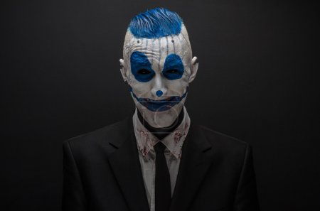 Photo pour Terrible clown et thème Halloween : clown bleu fou en costume noir isolé sur un fond sombre - image libre de droit
