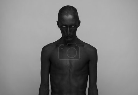 Photo for Gothic and Halloween theme: a man with black skin is isolated on a gray background in the studio, the Black Death - Royalty Free Image