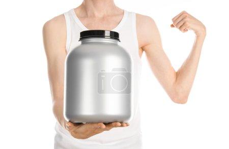 Photo pour Bodybuilding et Sport thème : un homme mince dans un T-shirt blanc et un jean tenant un pot en plastique avec une protéine isolée sur un fond blanc - image libre de droit