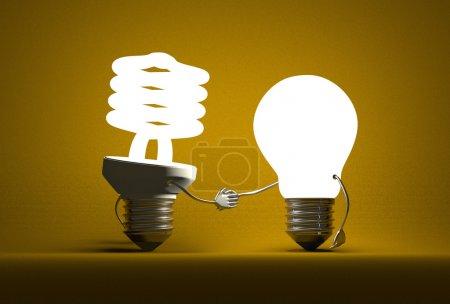 Photo pour Caractère lumineux de l'ampoule en spirale et tungstène une poignée de main sur fond texturé jaune foncé - image libre de droit