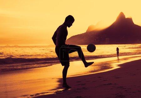 Guy playing soccer at beach at Rio at sunset