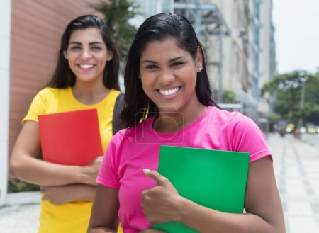 Photo for Two laughing latin female students outdoor in the city - Royalty Free Image
