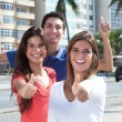 Three young people in the city showing thumb up...