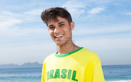 Brazilian sports fan at beach laughing at camera