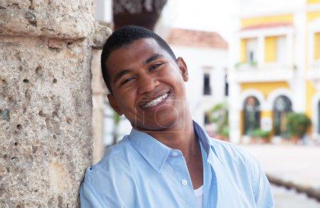 Photo pour Homme moderne en chemise bleue dans une ville coloniale avec des bâtiments historiques en arrière-plan - image libre de droit
