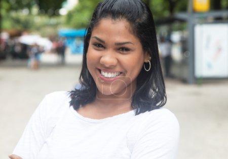 Photo pour Femme latine native riante dans une chemise blanche en ville avec rue et bâtiment en arrière-plan - image libre de droit