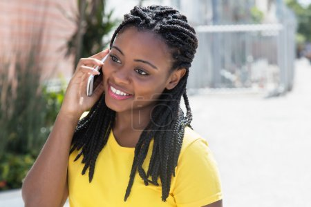 Laughing african american woman in a yellow shirt at mobile phon