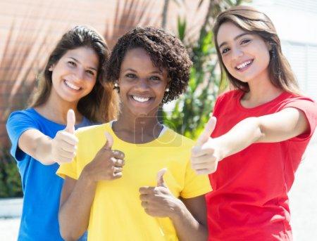 Photo pour Copines afro-américaines et caucasiennes en chemises colorées montrant pouces dans la ville avec des constructions modernes et des arbres en arrière-plan - image libre de droit
