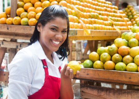Mexican saleswoman offering oranges on a farmers market