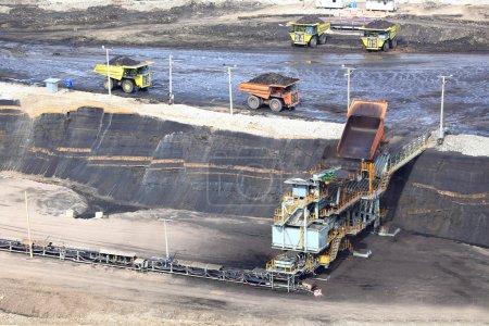 Photo pour Camions à benne basculante de construction lourde vidange de charbon au convoyeur à la mine de charbon - image libre de droit