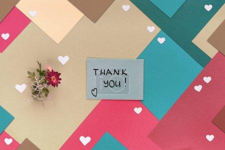 International Merci jour. Carte de voeux avec petite forme de coeur confettis et fleurs d'hiver Janvier. Concept géométrique créatif plat posé sur fond de papier stratifié. Merci ext sur la carte.
