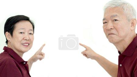 Asian senior couple pointing white isolate backgroun