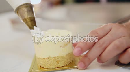 Hands squeezing  whipped cream pastry bag to decorate the cake topping
