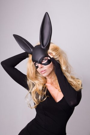 Beautiful blonde-haired young woman in carnival mask ballroom rabbit with long ears sensual sexy in a black dress, standing defiantly on a white background.