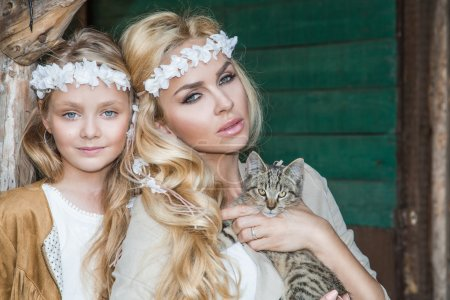 A beautiful blond woman with a baby girl snuggling on the wild west in white costumes with a cat on hands