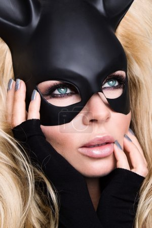 Beautiful sexy young woman with long blond curly hair in a black mask carnival ballroom rabbit with long ears sensual sexy in a black dress with fabric, standing defiantly on a clean, white, gray background holding hands up and holds