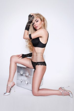 Blond hair Beautiful sexy young woman in lacy black underwear sitting on a silver cube with crystals