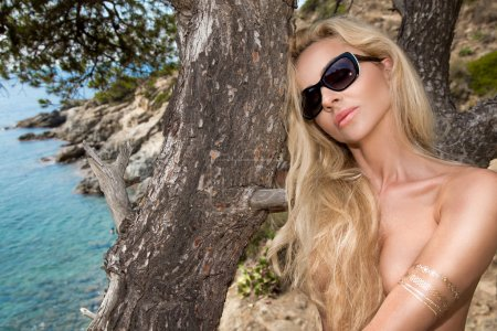 Beautiful blonde sexy woman with long legs in sunglasses and fantastic crystal dress and nudes  on rocks overlooking the blue sea with waves in the background clouds and blue sky and tree big dry brown