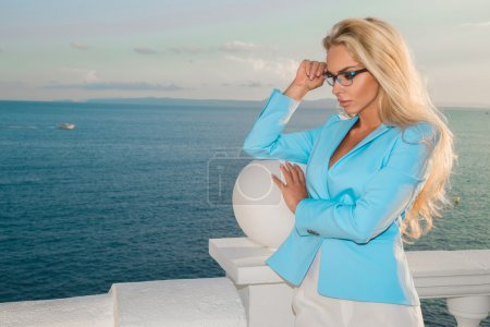 Beautiful blond hair sexy woman young girl model in sunglasses in blue dress, elegant jacket with crystals around the pool with a balustrade overlooking the sea and the island of Santorini