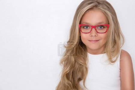 Photo for Portrait of a lovely little girl daughter in long blond hair and white dress and red glasses with white dots looks at the camera, photo on the white background amazing eyes - Royalty Free Image