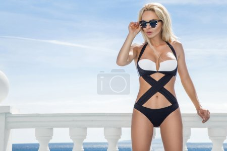 Beautiful blond hair sexy woman young girl model in sunglasses and elegant white and black sexy swimsuit, lace lingerie around the pool with a balustrade overlooking the sea and the island of Santorini