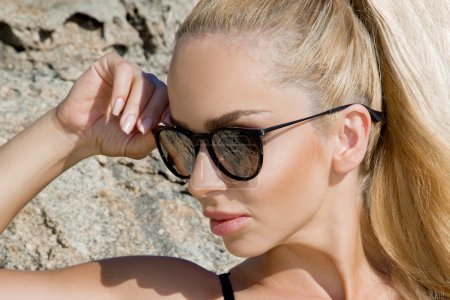Beautiful blond hair sexy woman young girl model in sunglasses and elegant black sexy swimsuit, lace lingerie overlooking the sea, the rocks and the island of Santorini