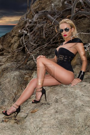 Beautiful blond hair sexy woman young girl model in sunglasses and elegant black and gold sexy swimsuit lingerie with crystals around  sea and the island of Santorini