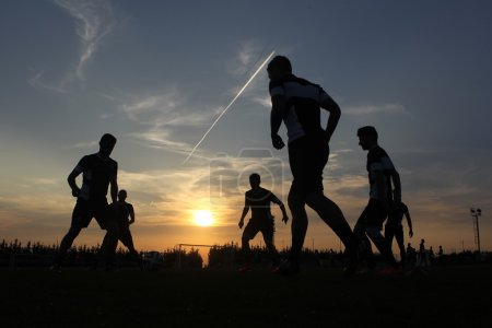 Silhouettes of footballers on the sunset sky