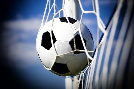 Soccer football in Goal net with sky field. Vignette Lens
