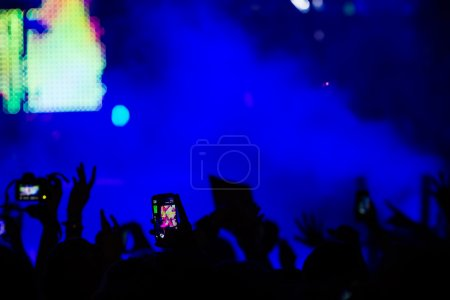Photo for People taking photographs with touch smart phone during a music entertainment public concert - Royalty Free Image